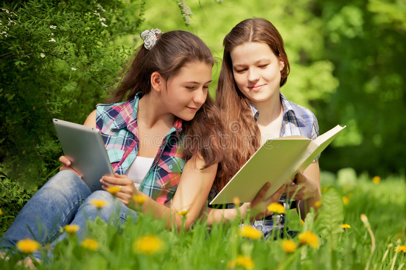 Teenagers in the park. book or computer. Concept. Teenagers girls in the park. books or computer. Concept royalty free stock photos