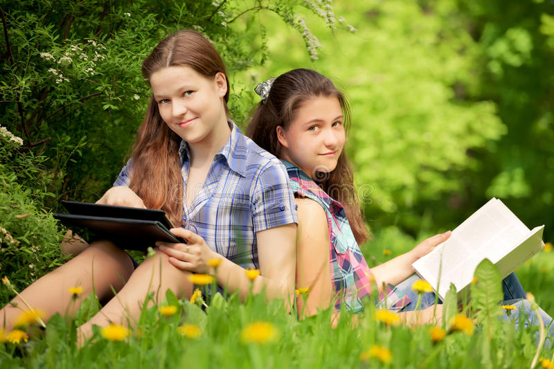 Teenagers in the park. bookr or computer. Concept. Teenagers girls in the park. books or computer. Concept stock image