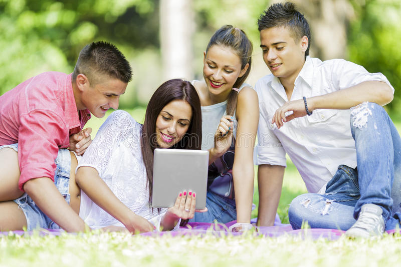 Teenagers in the park. With tablet stock photo
