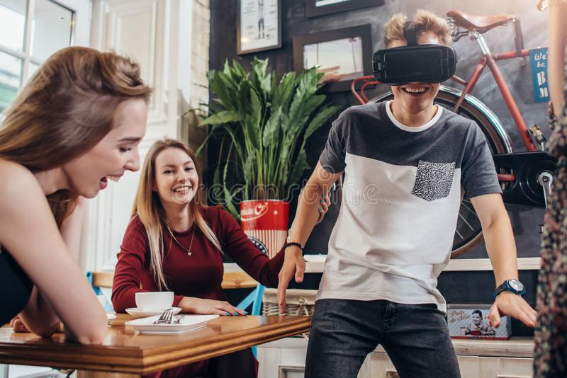 Teenagers passing leisure time by testing virtual reality helmet playing funny games at home stock images