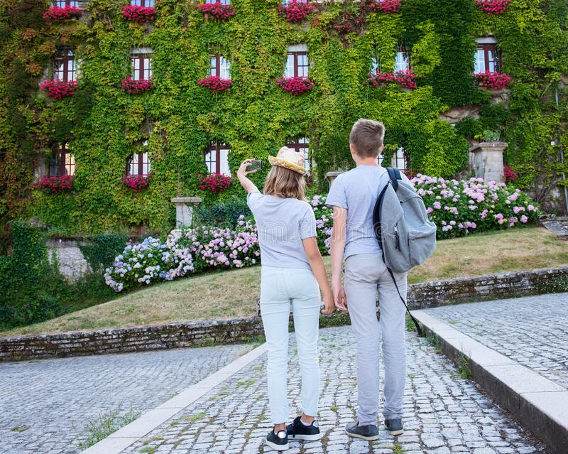Teenagers people and travel concept. Teens walking and making photos in the street of an old town, historical centre of the town, royalty free stock image
