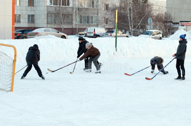 Teenagers play hockey on a domestic skating rink. Tyumen, Russia. February, 2016 royalty free stock photography