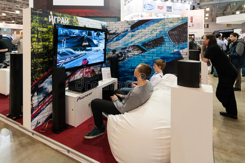 Teenagers play video games at Pioneer stand stock photo