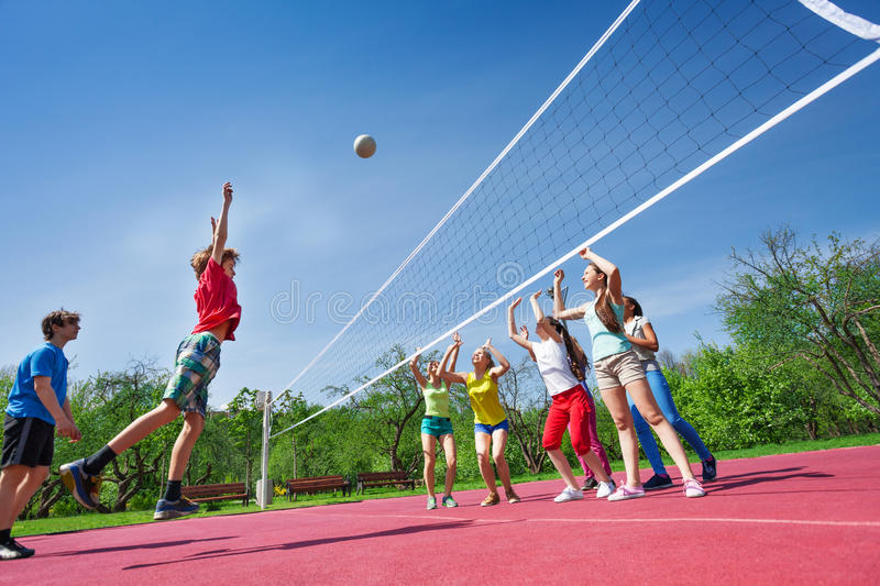Teenagers play volleyball game on playing ground. Teenagers play volleyball game on the playing ground during sunny summer day outside royalty free stock image
