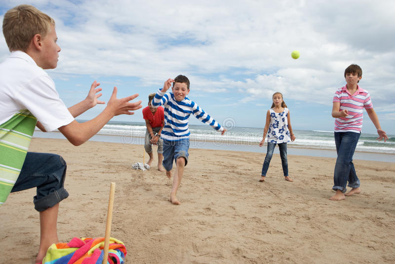 Teenagers playing baseball on beach stock images
