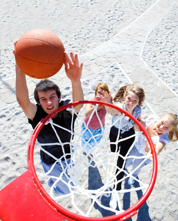 Teenagers playing basketball royalty free stock images