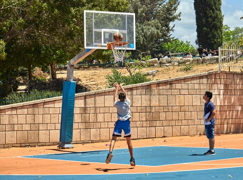 Teenagers playing basketball in a city park royalty free stock photography