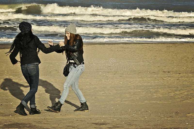 Teenagers playing in the beach royalty free stock images