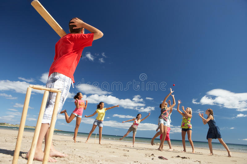 Teenagers playing cricket on beach stock photography