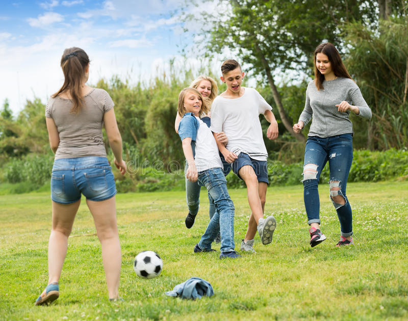 Teenagers playing football in park royalty free stock photography