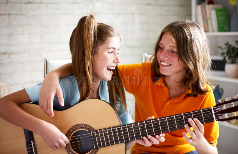 Teenagers playing guitar stock images