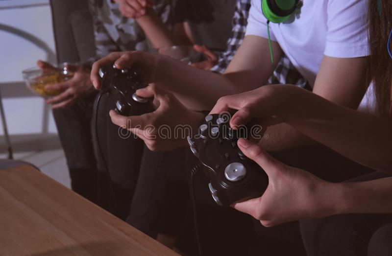 Teenagers playing video games at home late in the evening, closeup stock photos