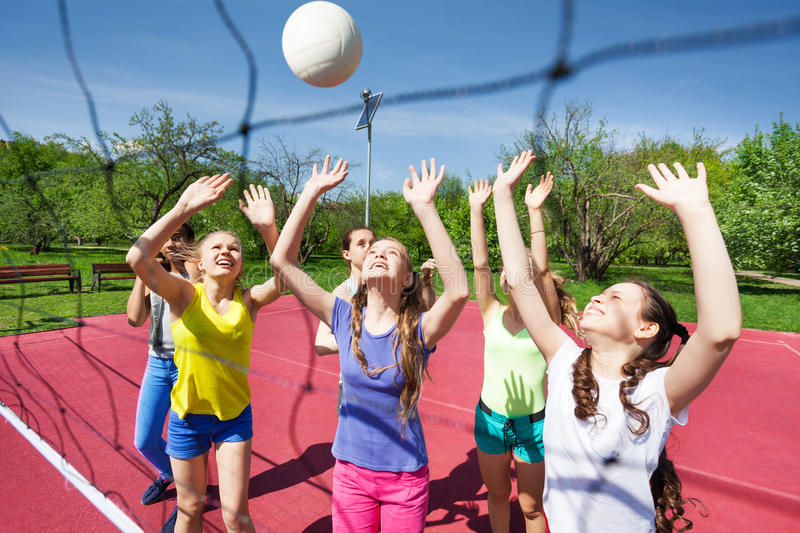 Teenagers are playing volleyball together near net royalty free stock image