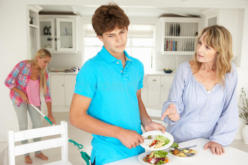 Teenagers reluctant to do housework. Clearing dishes stock image