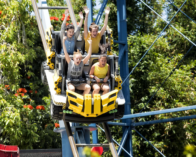 Teenagers on a roller coaster. Three teenage girls and a fourth girl age twelve are speeding down the initial steep portion of a roller coaster. Their hands are stock image
