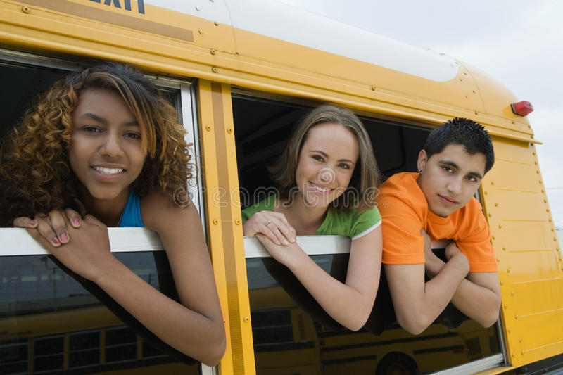 Teenagers On School Bus. Portrait of teenagers looking out from windows of a yellow school bus stock image