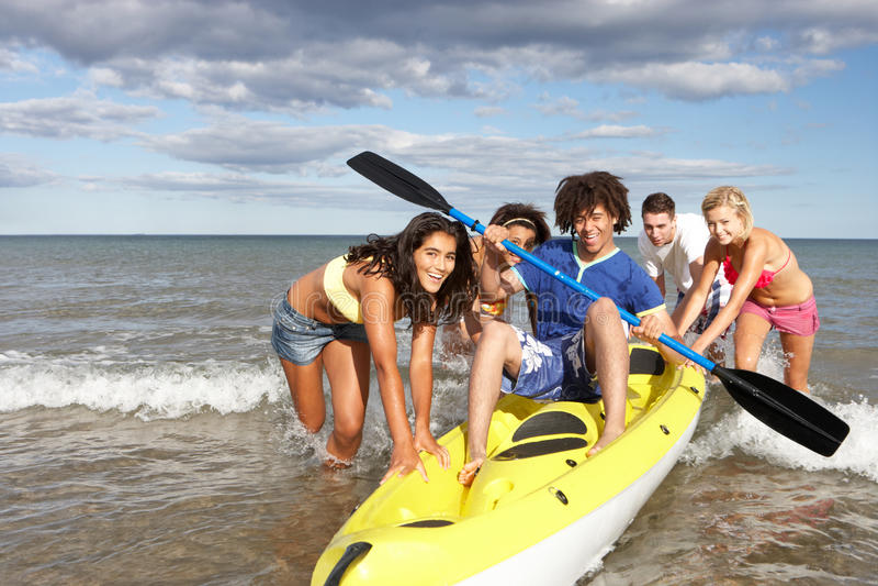 Teenagers in sea with canoe stock image