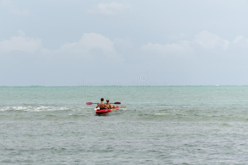 Teenagers at sea with a canoe royalty free stock photo