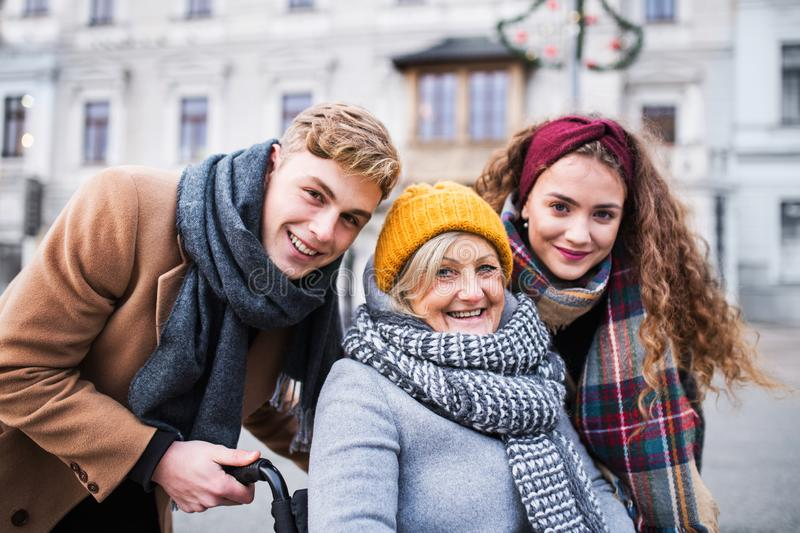 Teenagers and senior grandmother in wheelchair on the street in winter. stock photography