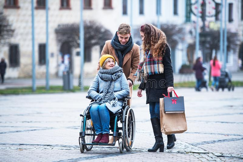 Teenagers and senior grandmother in wheelchair walking down the street in winter. stock photography
