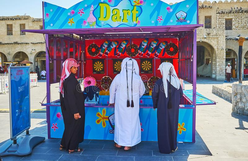 Teenagers in shooting range, Souq Waqif, Doha, Qatar. DOHA, QATAR - FEBRUARY 13, 2018: The teenagers in traditional Arabic attire at the counter of shooting royalty free stock photo