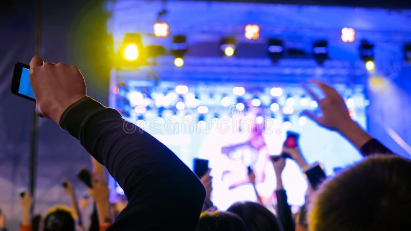 Teenagers silhouette partying at night open air concert in front of the stage stock image