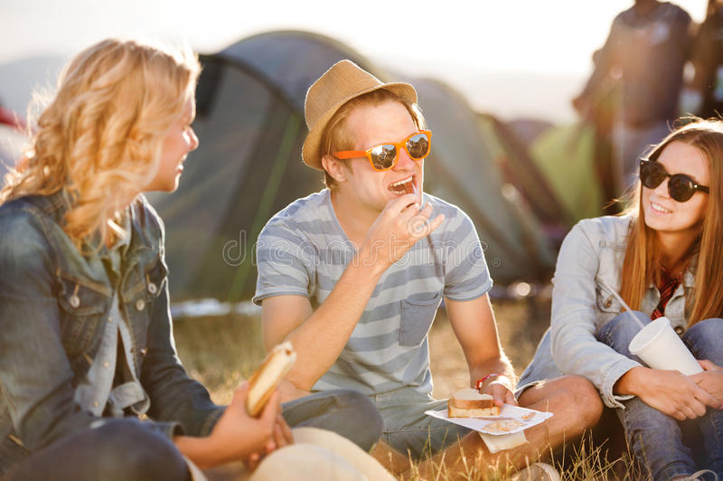 Teenagers sitting on the ground in front of tents, resting stock photos