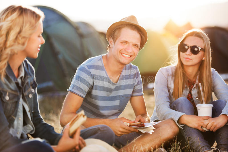 Teenagers sitting on the ground in front of tents, resting royalty free stock photography