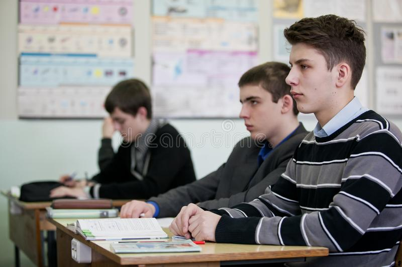 Teenagers sitting at one desk and listening to their teacher stock photo