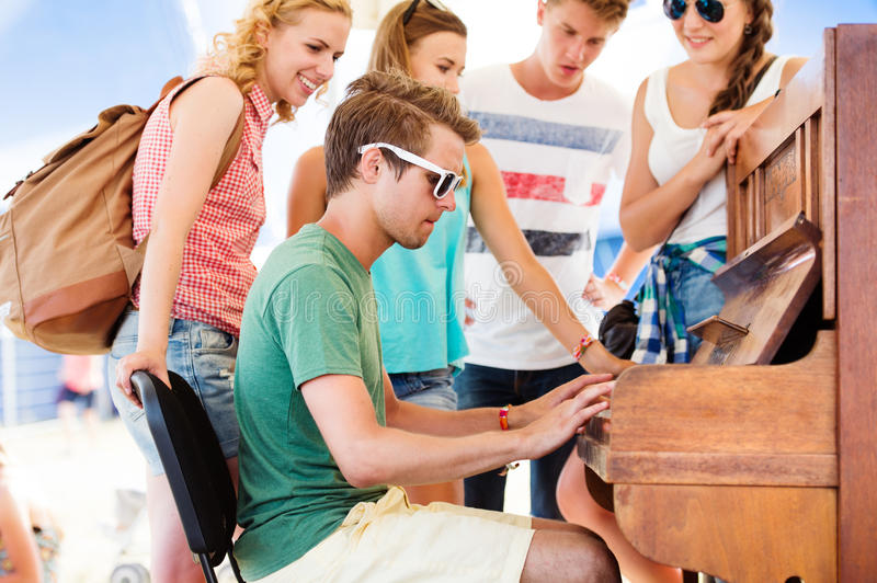 Teenagers at summer music festival, boy plays the piano royalty free stock photos