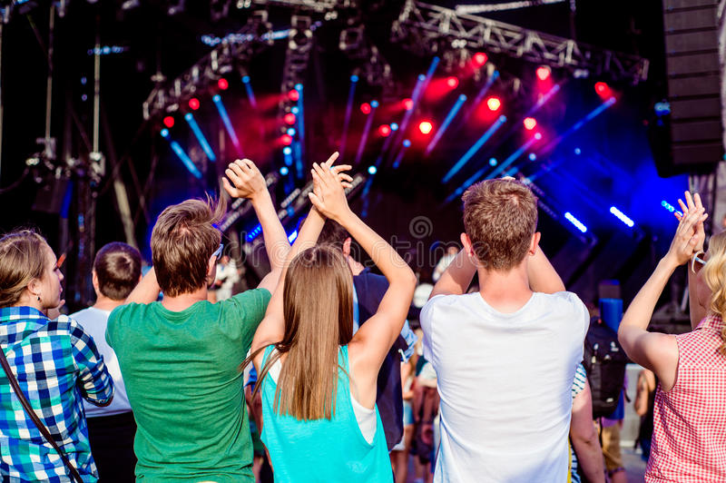 Teenagers at summer music festival clapping and singing. Teenagers at summer music festival against the stage in a crowd enjoying themselves, clapping, back view stock images