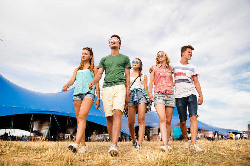 Teenagers at summer music festival in front of big blue tent royalty free stock image