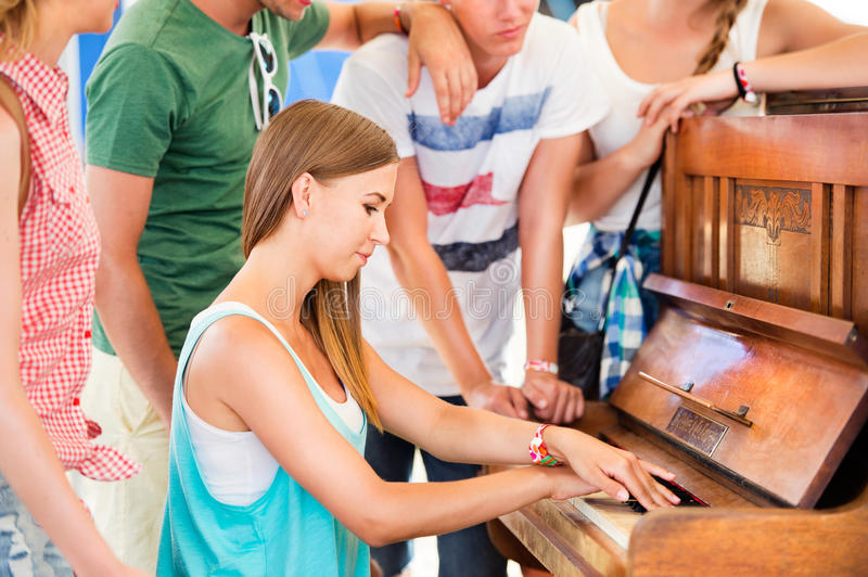 Teenagers at summer music festival, girl plays the piano royalty free stock photos