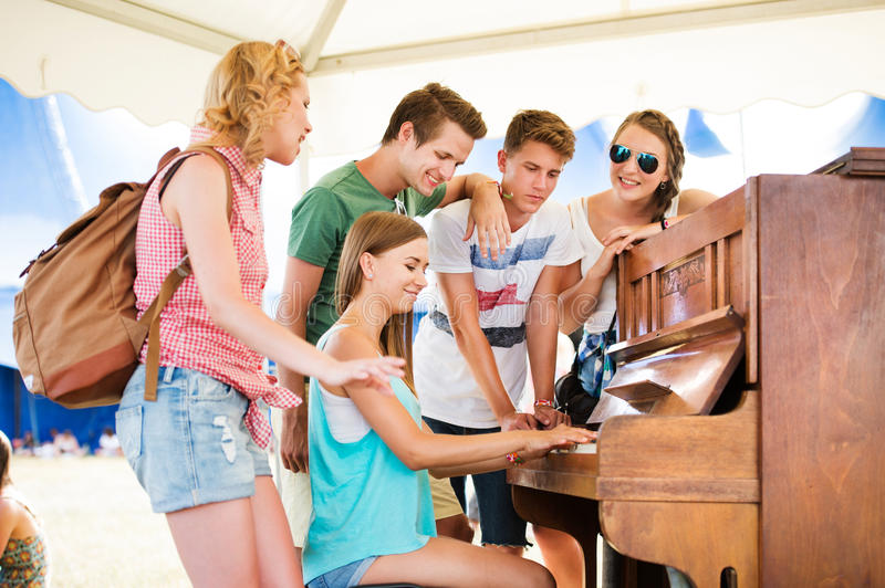 Teenagers at summer music festival, girl plays the piano royalty free stock image