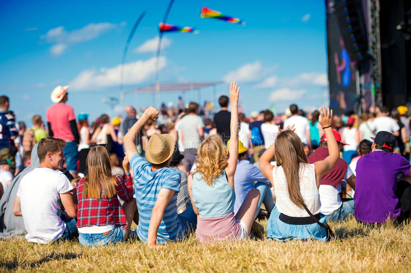 Teenagers, summer music festival, sitting in front of stage stock photography