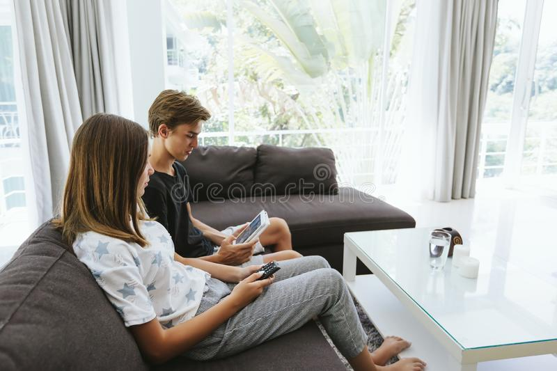 Teenagers using tablet pc on couch royalty free stock image