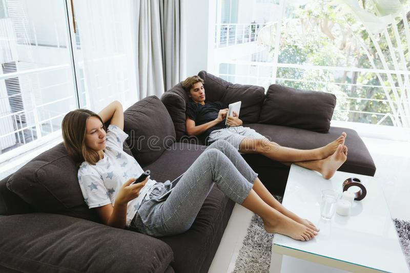 Teenagers using tablet pc and watching tv on couch stock photos
