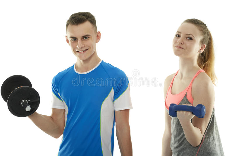 Teenagers working out with dumbbells. Teenagers boy and girl doing a fitness workout with dumbbells stock image