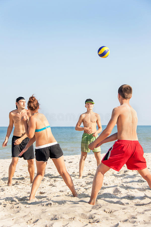 Teenages friends (four people) are playing volleyball on the beach. royalty free stock photos