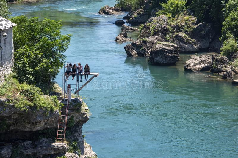 Teenages sit on a diving paltform over the river watching drivers leap from the Stari Most bridge stock image
