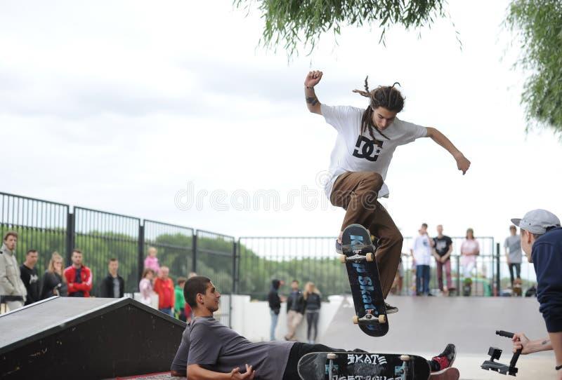 Teenargers tem uma competição amigável do skate em Gomel Fragmento de um skater, que faça o salto fotografia de stock royalty free