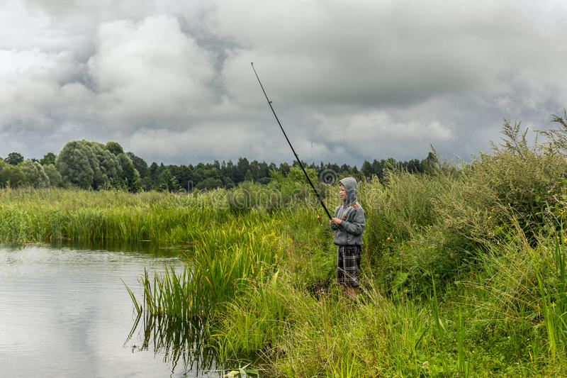 Teenboy fiske på den lilla floden royaltyfri fotografi