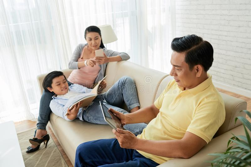 Family enjoying weekend at home. Teenge boy reading book when his parents checking news or watching videos on their gadgets royalty free stock photo