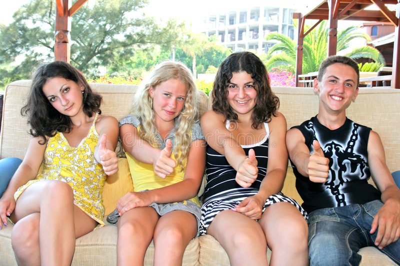 Teens. Pretty blond and brunette girls and boy having fun on the sofa stock image