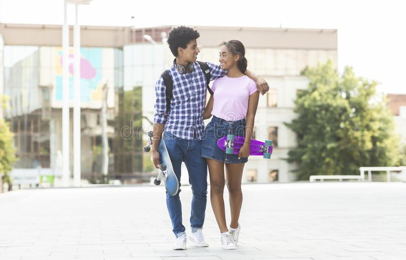 Teens dating in the city walking together outdoors royalty free stock image