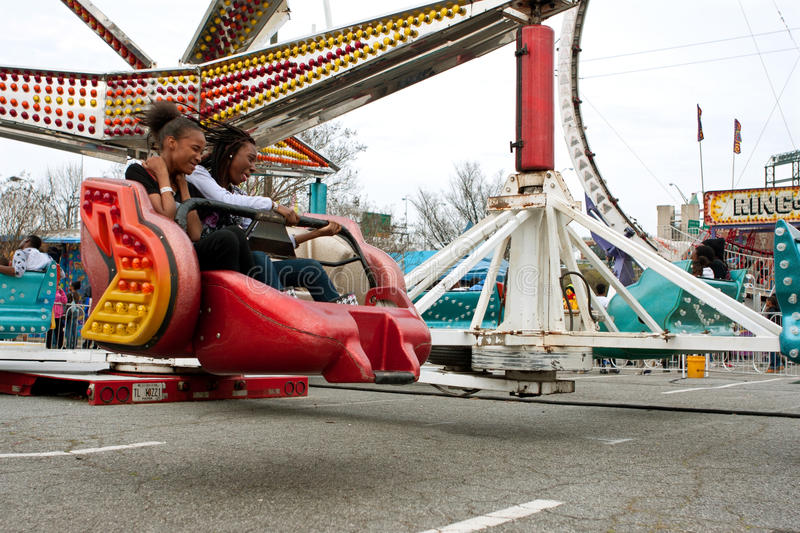 Teens Enjoy Fast Moving Carnival Ride At Fair stock photography