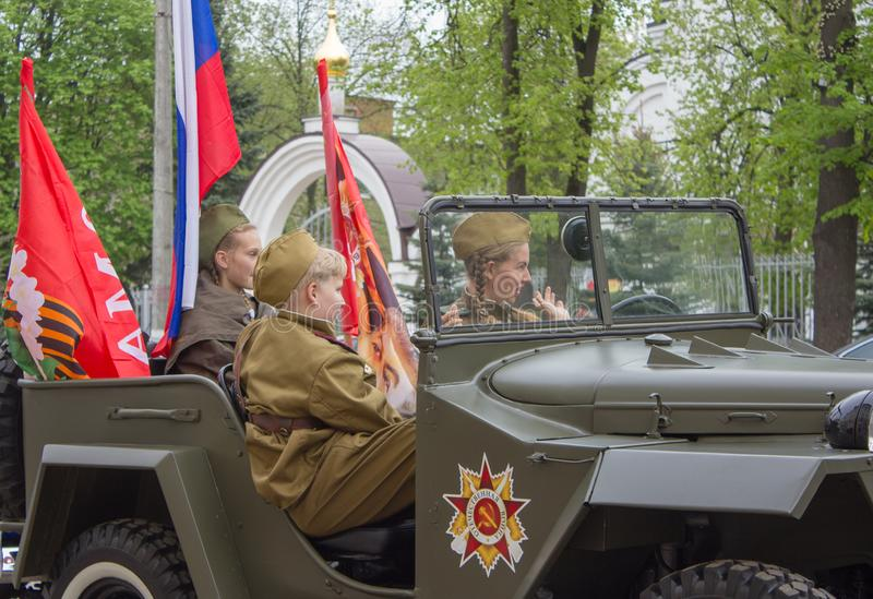 Teens in the form of a Russian soldier in a military car. Fryazino, Moscow region / Russian Federation 05.09.2019..Motor race in honor of Victory Day. Guy in a royalty free stock image