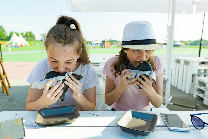 Teens girls with an appetite eats black fast food burger. Summer street cafe, recreation area, city park background. Teens girls with an appetite eats black stock photo