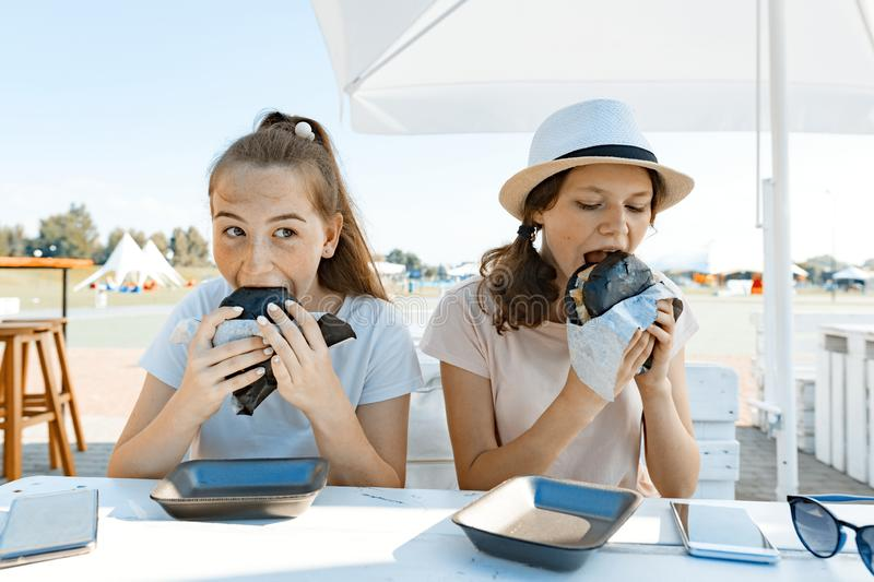 Teens girls with an appetite eats black fast food burger. Summer street cafe, recreation area, city park background.  stock images