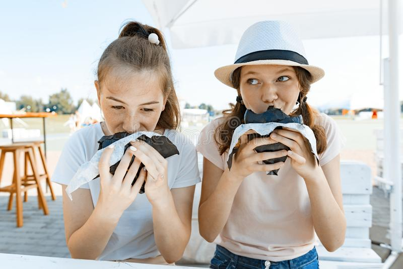 Teens girls with an appetite eats black fast food burger. Summer street cafe, recreation area, city park background.  stock photo